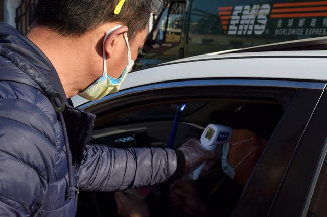 A volunteer measures the body temperature of a driver at an entrance to a residential compound following an outbreak of the coronavirus disease (COVID-19), in Suifenhe, a city bordering Russia in China's Heilongjiang province, April 15, 2020.  REUTERS/Huizhong Wu