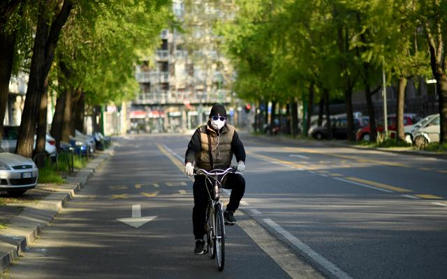A man wearing a protective face mask rides a bicycle, amid the coronavirus disease (COVID-19) outbreak in Milan, Italy April 9, 2020. REUTERS/Daniele Mascolo