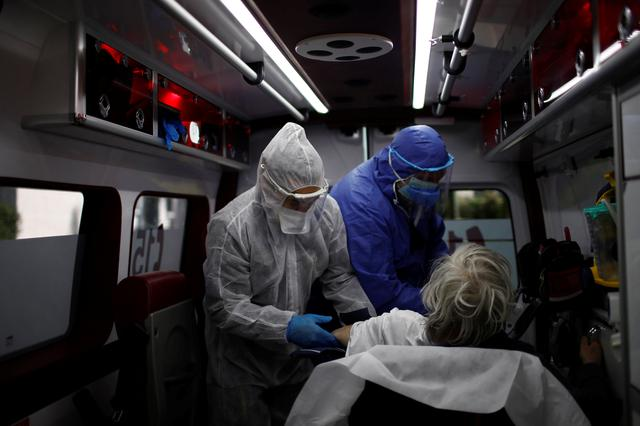 French ambulance men, wearing protective suits and masks, transport to an hospital a man suspected of being infected with the coronavirus disease in their ambulance in Mennecy near Paris as the spread of the coronavirus disease (COVID-19) continues in France April 15, 2020.  REUTERS/Gonzalo Fuentes
