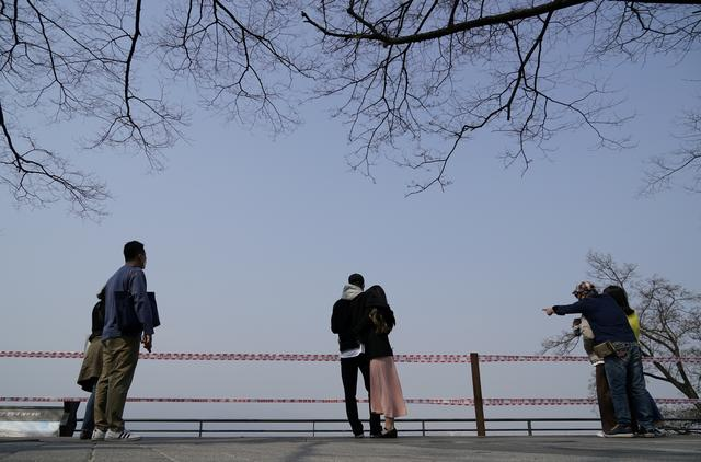 FILE PHOTO: Couples enjoy a view of Seoul while practicing social distancing, behind an observation deck which has been cordoned off as part of efforts to avoid the spread of the coronavirus disease (COVID-19), atop Mt. Namsan in Seoul, South Korea, April 7, 2020. REUTERS/Kim Hong-Ji