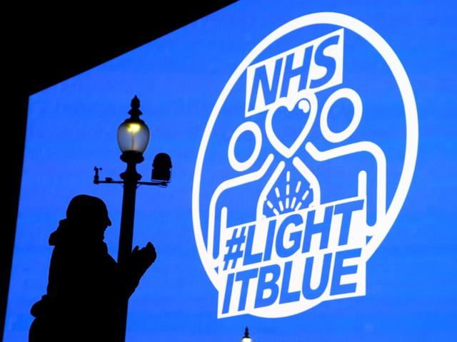 FILE PHOTO: People applaud in front of big screen in Piccadilly Circus during the Clap For Our Carers campaign in support of the NHS, as the spread of the coronavirus disease (COVID-19) continues, London, Britain, March 26, 2020. REUTERS/Toby Melville