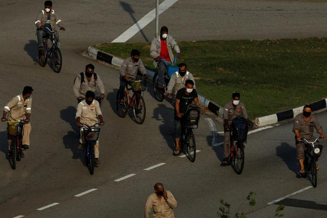 Migrant workers ride back to their dormitories after work, during the outbreak of coronavirus (COVID-19), in Singapore April 16, 2020. REUTERS/Edgar Su