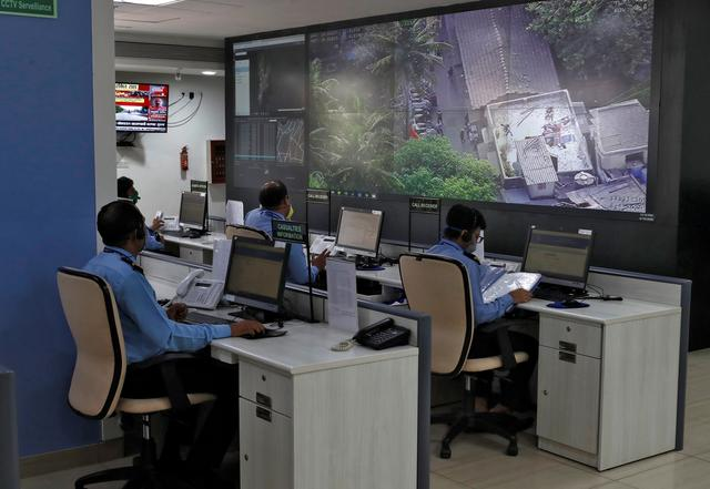"FILE PHOTO: Staff members of Brihanmumbai Municipal Corporation (BMC) watch large screens to monitor the movement of people on the roads, inside a ""war room"" focused on halting the spread of the coronavirus disease (COVID-19), in Mumbai, India, April 10, 2020. REUTERS/Francis Mascarenhas/File Photo"