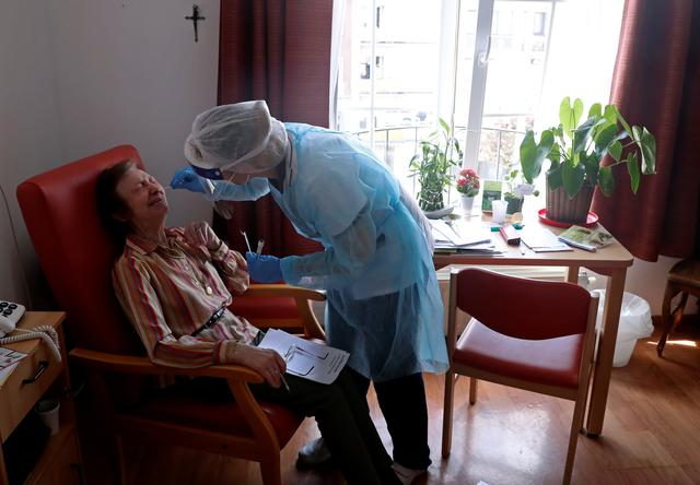 An employee at an elderly residence checks a woman for coronavirus disease (COVID-19) as part of a series of tests performed among seniors in the country, in Brussels, Belgium, April 16, 2020. REUTERS/Yves Herman