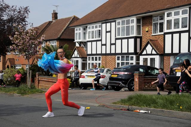 Elyse Blemmings, also known as the Mancunian Motivator leads residents of Chigwell Park Drive in a fitness class outside their homes in Chigwell, Britain April 16, 2020. REUTERS/Simon Dawson