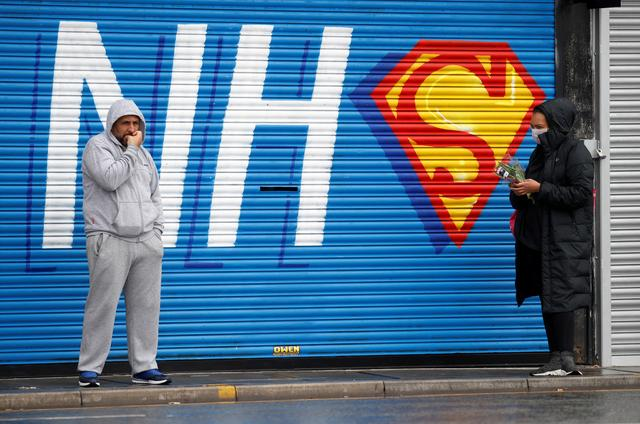 Two people practicing social distancing in front of graffiti in support of the NHS, as the spread of the coronavirus disease (COVID-19) continues, Liverpool, Britain, April 18, 2020. REUTERS/Phil Noble