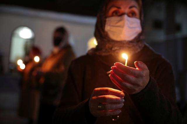 A believer wearing a protective mask holds a candle outside a church during an Orthodox Easter service, amid the coronavirus disease (COVID-19) outbreak in Marneuli, Georgia April 18, 2020. Picture taken April 18, 2020.  REUTERS/Irakli Gedenidze