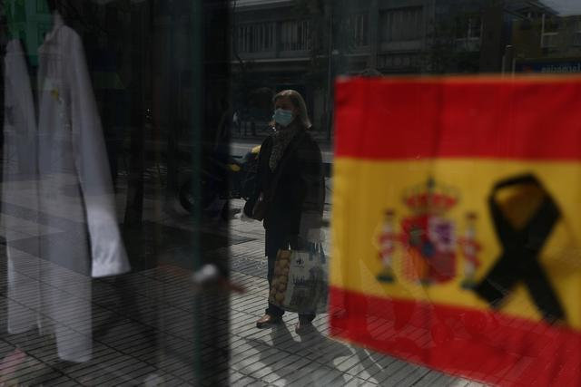 A woman wearing a protective mask waits to enter a pharmacy displaying a Spanish flag with a black ribbon, amid the coronavirus disease (COVID-19) outbreak in Madrid, Spain, April 18, 2020. REUTERS/Susana Vera