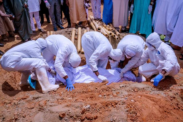 Men wearing protective gear bury the body of Nigerian president's chief of staff, Abba Kyari, who died on Friday after contracting the coronavirus disease (COVID-19), at Gudu Cemetery in Abuja, Nigeria April 18, 2020. Nigeria Presidency/Handout via REUTERS