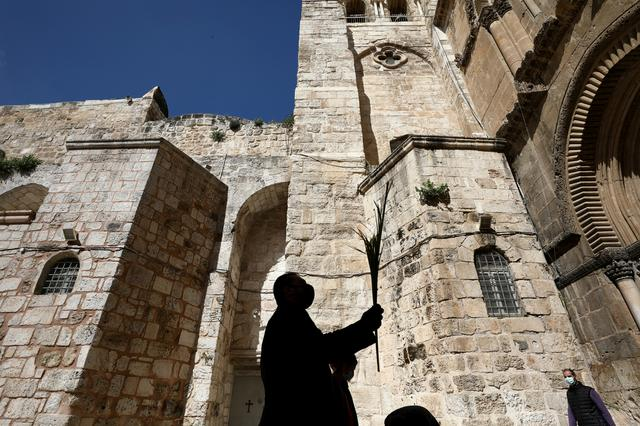FILE PHOTO: An Orthodox Christian worshipper is silhouetted as he holds a palm frond outside the closed doors of the Church of the Holy Sepulchre on Orthodox Palm Sunday amid the coronavirus disease (COVID-19) outbreak, in Jerusalem's Old City April 12, 2020. REUTERS/Ammar Awad/ FIle Photo