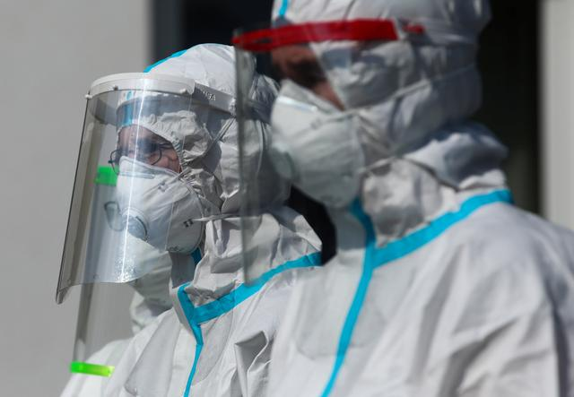 FILE PHOTO: Health workers wearing protective gear are seen at the territory of a nursing home, where multiple confirmed cases of the coronavirus disease (COVID-19) among the facility staff and residents were reported, in Bochnia, Poland, April 13, 2020. Jakub Wlodek/Agencja Gazeta via REUTERS