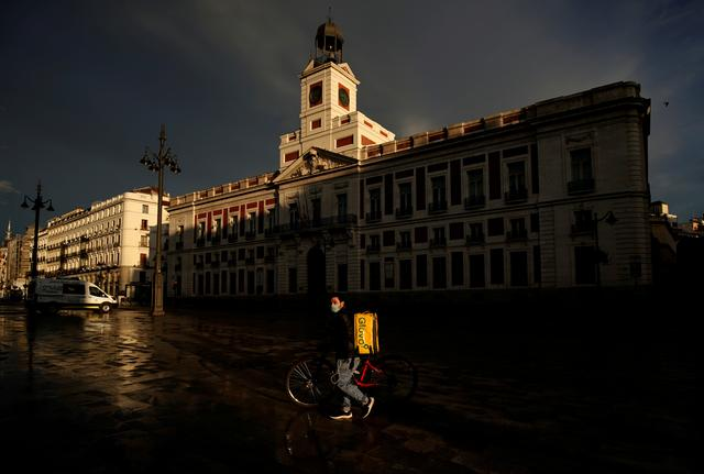A Glovo food delivery courier wearing a face mask walks past a deserted Puerta del Sol square during the lockdown following the coronavirus disease (COVID-19) outbreak in Madrid, Spain, April 19, 2020. REUTERS/Juan Medina