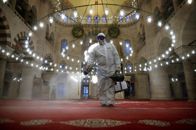 FILE PHOTO: A municipality worker in a protective suit disinfects Kilic Ali Pasha Mosque due to coronavirus concerns in Istanbul, Turkey March 11, 2020. REUTERS/Kemal Aslan