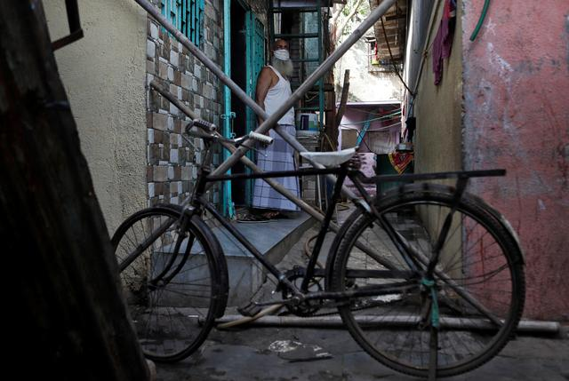 FILE PHOTO: A man stands behind a makeshift barricade set up to stop people from entering a lane, during a nationwide lockdown in India to slow the spread of COVID-19, in Dharavi, one of Asia's largest slums, during the coronavirus disease outbreak, in Mumbai, India, April 9, 2020. REUTERS/Francis Mascarenhas
