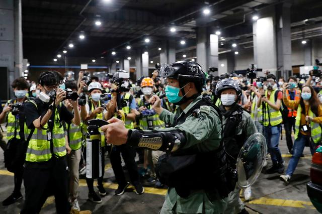 FILE PHOTO: File photo of a riot police officer holding a pepper spray as he tries to disperse anti-government protesters after a vigil to mourn student's death, in Hong Kong, China March 8, 2020. REUTERS/Tyrone Siu
