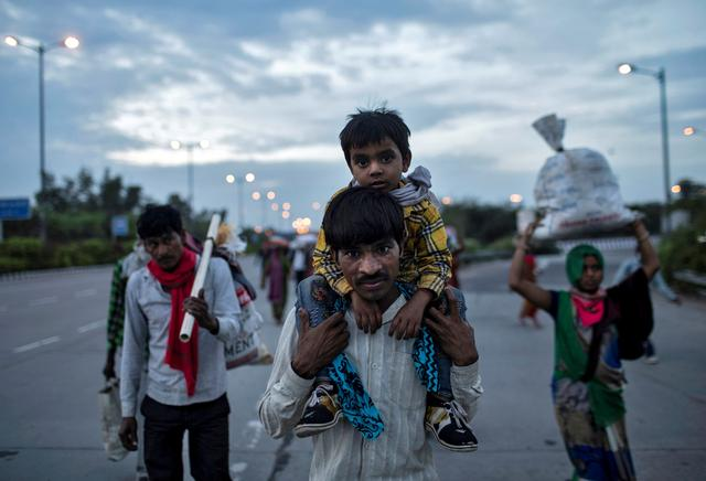 FILE PHOTO: Dayaram Kushwaha, a migrant worker, carries his 5-year-old son, Shivam, on his shoulders as they walk along a road to return to their village, during a 21-day nationwide lockdown to limit the spreading of coronavirus,   in New Delhi, India, March 26, 2020.  REUTERS/Danish Siddiqui