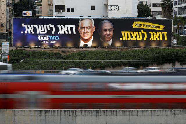 FILE PHOTO: Traffic moves past a Blue and White party election campaign poster, depicting party leader Benny Gantz, and Israeli Prime Minister Benjamin Netanyahu, in Tel Aviv, Israel February 18, 2020. REUTERS/Amir Cohen/File Photo