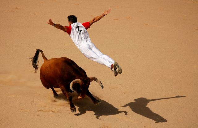 FILE PHOTO: A recortador jumps over a bull during a contest in a bullring at the San Fermin festival in Pamplona, Spain, July 13, 2019. REUTERS/Jon Nazca/File Photo