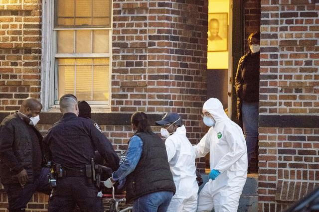 FILE PHOTO: A woman watches as an officer from the New York Police Department helps workers carry a body out of a house amid the coronavirus disease (COVID-19) outbreak, in the Brooklyn borough of New York City, U.S., April 20, 2020. REUTERS/Lucas Jackson