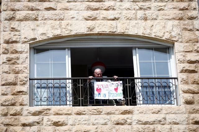 "Elias Feinzilberg, a 102-year-old Holocaust survivor, stands at the window of his home in Jerusalem as Israel marks Holocaust Remembrance Day under coronavirus disease (COVID-19) restrictions, April 21, 2020. The Hebrew words on the placard read: ""Remembering close-by, embracing from afar."" REUTERS/Ronen Zvulun"