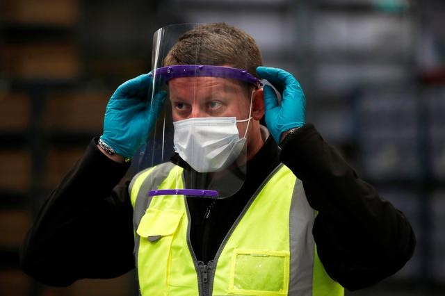 An employee uses a visor at the Nissan plant, as Nissan produces visors for the NHS, amid the outbreak of the coronavirus disease (COVID-19), in Sunderland, Britain, April 21, 2020. REUTERS/Lee Smith
