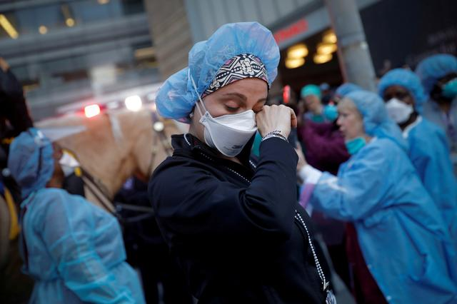 FILE PHOTO: A nurse wipes away tears as she stands outside NYU Langone Medical Center on 1st Avenue in Manhattan as New York Police Department (NYPD) Mounted Police and other units came to cheer and thank healthcare workers at 7pm during the outbreak of the coronavirus disease (COVID-19) in New York City, New York, U.S., April 16, 2020. REUTERS/Mike Segar
