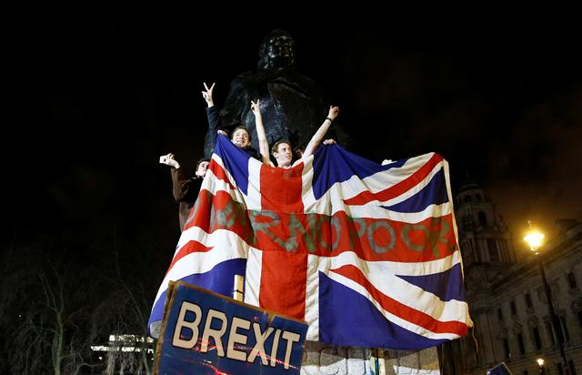 FILE PHOTO: People celebrate at the statue of Winston Churchill as Britain leaves the EU on Brexit day in London, Britain, January 31, 2020. REUTERS/Henry Nicholls