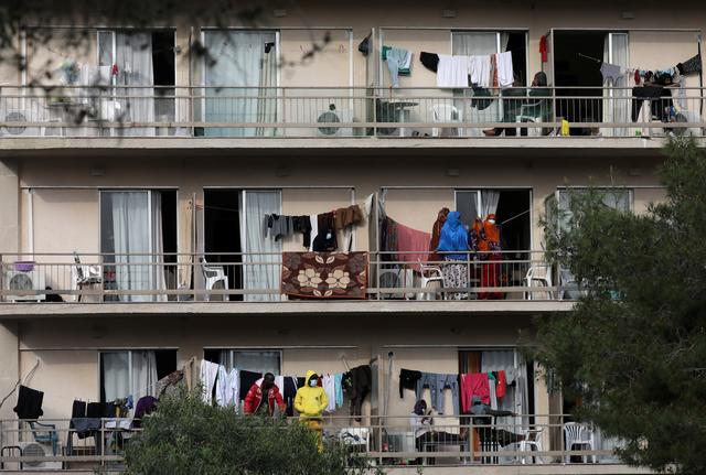 Migrants are pictured in the balconies of a hotel used as a refugee shelter, after authorities found several cases of the novel coronavirus and put the area under quarantine, following the outbreak of the coronavirus disease (COVID-19), in Kranidi, Greece April 21, 2020. REUTERS/Costas Baltas