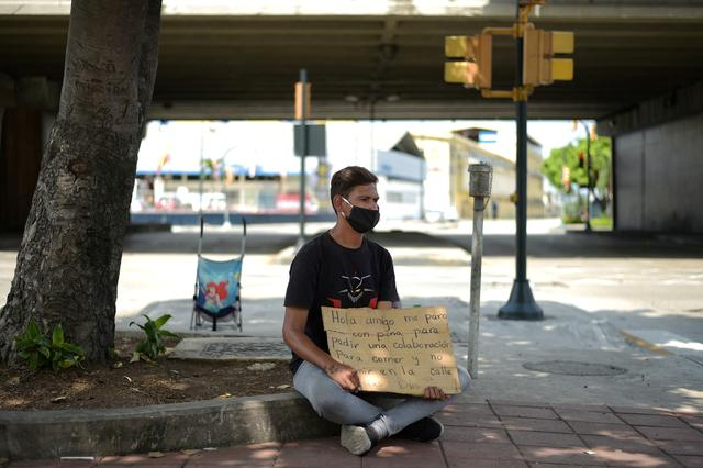 A Venezuelan immigrant makes a plea for money on a street corner to help him and his family return home to Venezuela amid the spread of the coronavirus disease (COVID-19), in Guayaquil, Ecuador April 20, 2020. REUTERS/Vicente Gaibor del Pino