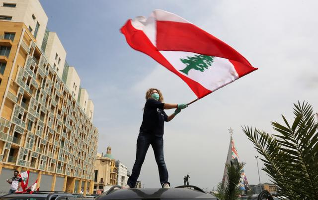 An anti-government demonstrator holds a Lebanese flag as she stands on top of her car, during a countrywide lockdown to combat the spread of the coronavirus disease (COVID-19), in Beirut, Lebanon April 21, 2020. REUTERS/Aziz Taher
