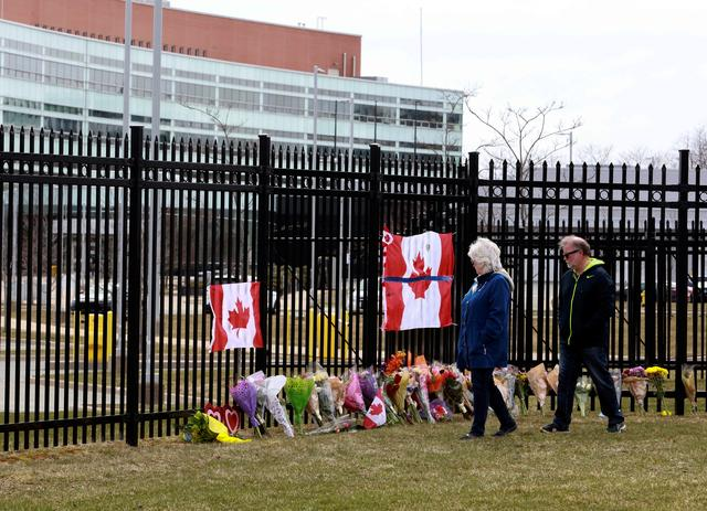 Two individuals observe the flowers of a memorial at the Royal Canadian Mounted Police (RCMP) Headquarters, in Dartmouth, Nova Scotia, Canada April 20, 2020. REUTERS/John Morris