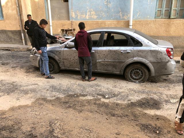 FILE PHOTO: Libyan boys check a damaged car after a shell fell on a residential area at Hadba al-Badri district, in Tripoli, Libya January 28, 2020. REUTERS/Ismail Zitouny/File Photo