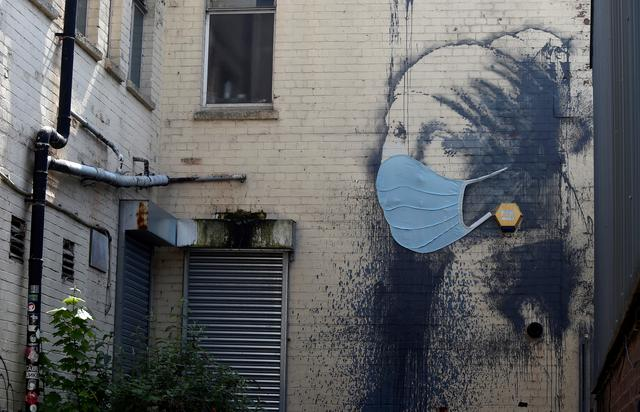 "A piece of Banksy street art titled ""The Girl with the Pierced Eardrum"", now adorned with a protective face mask, is seen at Albion Dock, amid the spread of the coronavirus disease (COVID-19), in Bristol, Britain April 23, 2020. REUTERS/Rebecca Naden"