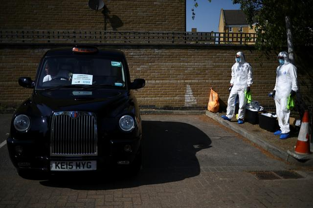 Workers from cleaning company Dropless wait to sanitise a London Black Cab as part of a service between taxi platform Gett and the NHS in south east London to ensure patients with COVID-19 symptoms can get to a local GP without using public transport as the spread of the coronavirus disease (COVID-19) continues, in London, Britain, April 23, 2020. REUTERS/Hannah Mckay