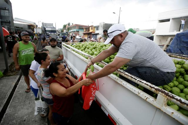 FILE PHOTO: A woman is given chayotes at a distribution point for fruits and vegetables donated by domestic producers unable to export due to the coronavirus disease (COVID-19), in San Jose, Costa Rica April 13, 2020. REUTERS/Juan Carlos Ulate/File Photo