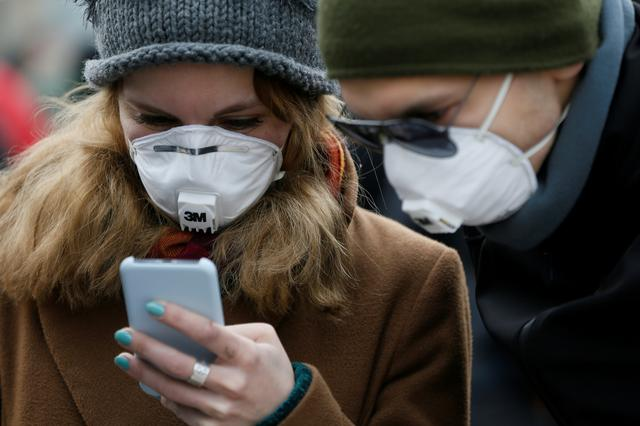 FILE PHOTO: People wearing protective face masks use a smartphone on a street amid coronavirus (COVID-19) concerns in Kiev, Ukraine March 17, 2020.  REUTERS/Valentyn Ogirenko