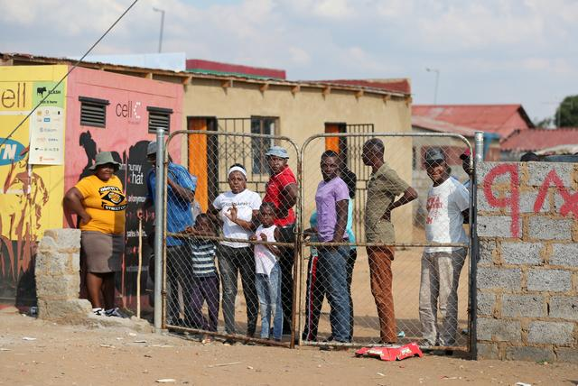 Residents look from behind a closed gate as members of the military patrol during a nationwide lockdown aimed at limiting the spread of the coronavirus disease (COVID-19), in Soweto, South Africa April 23, 2020. REUTERS/Siphiwe Sibeko     TPX IMAGES OF THE DAY