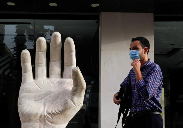 A man wearing a protective face mask walks near a granite symbol hand of peace, amid concerns over the coronavirus disease (COVID-19), in the Cairo suburb of Maadi, Egypt April 22, 2020. REUTERS/Amr Abdallah Dalsh