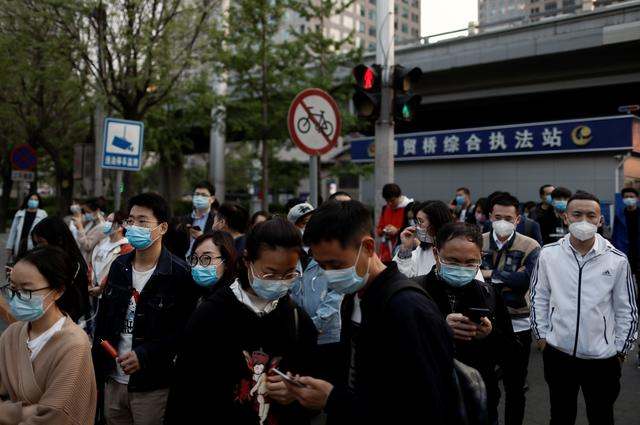 People wearing protective face masks leave work after office hours in Central Business District, as the spread of the new coronavirus disease (COVID-19) continues, in Beijing, China, April 17, 2020. REUTERS/Thomas Peter