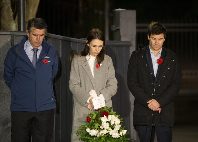 New Zealand Prime Minister Jacinda Ardern stands at dawn on the driveway of Premier House with her father Ross Ardern, and partner Clarke Gayford, in remembrance of ANZAC, as the traditional ANZAC service have been cancelled due to the coronavirus disease COVID-19 restrictions, in Wellington, New Zealand, April 25, 2020. Ross Giblin/Pool via REUTERS