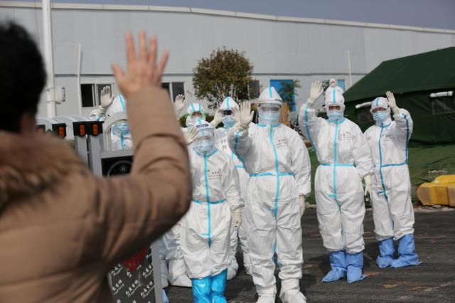 FILE PHOTO: Medical personnel in protective suits wave hands to a patient who is discharged from the Leishenshan Hospital after recovering from the novel coronavirus, in Wuhan, the epicentre of the novel coronavirus outbreak, in Hubei province, China March 1, 2020. China Daily via REUTERS/File Photo