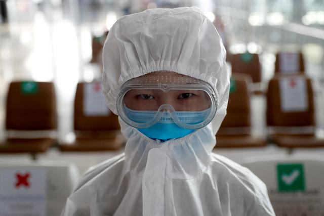 FILE PHOTO: A chinese student living in Thailand wears a protective suit as a measure of protection against the coronavirus disease (COVID-19) at the Suvarnabhumi Airport before boarding a repatriation flight, in Bangkok, Thailand, April 21, 2020. REUTERS/Jorge Silva
