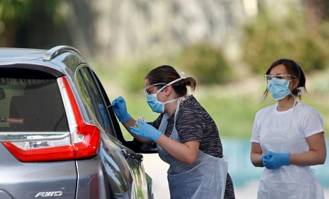 Medical workers conduct coronavirus disease (COVID-19) check-ups at a drive-thru testing site in Chessington, London, Britain, April 24, 2020. REUTERS/Henry Nicholls