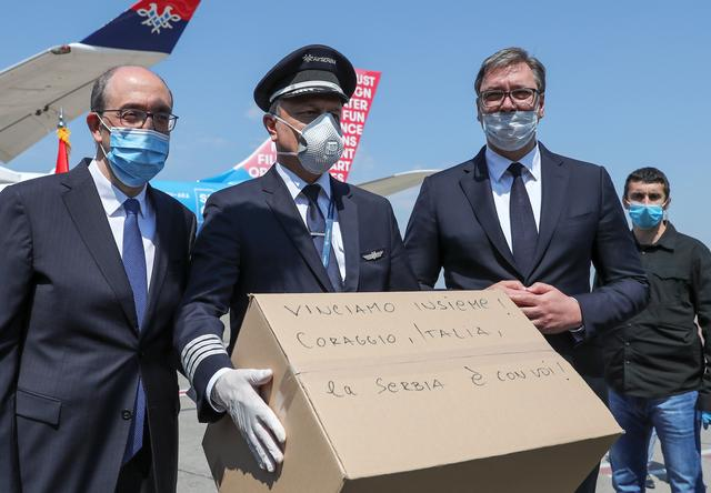 "Serbian President Aleksandar Vucic wearing a protective face mask poses next to the pilot holding one of the packages with medical supplies, the writing on it reads: ""Let's win together! Courage, Italy, Serbia is with you!"" at Nikola Tesla Airport, where planes with medical supplies are set to fly to Italy to help the fight against the coronavirus disease (COVID-19) outbreak, in Belgrade, Serbia April 25, 2020. REUTERS/Marko Djurica"