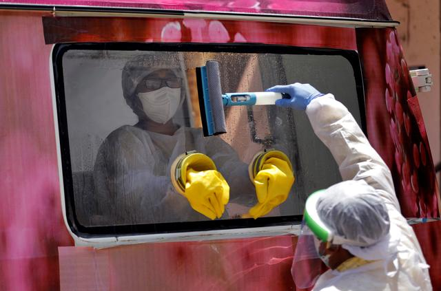 A medical worker sits inside a mobile test van for the coronavirus disease (COVID-19) after she collected swabs from people to test, on the outskirts of Ahmedabad, India, April 27, 2020. REUTERS/Amit Dave