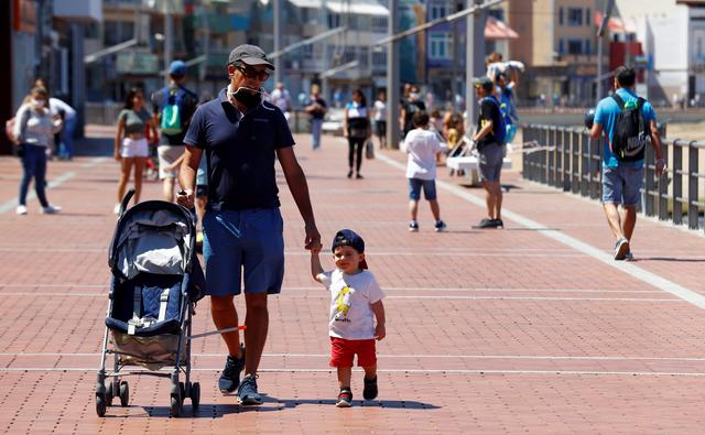 Children walk with their parents at promenade of Las Canteras beach after restrictions were partially lifted for children for the first time in six weeks, following the coronavirus disease (COVID-19) outbreak on the island of Gran Canaria, Spain, April 26, 2020. REUTERS/Borja Suarez