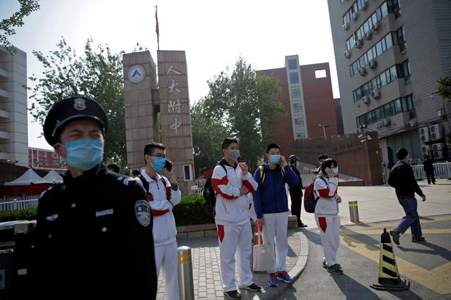 FILE PHOTO: Students wearing face masks leave a school in Beijing, China as senior high school students in the Chinese capital returned to campus following the coronavirus disease (COVID-19) outbreak, April 27, 2020. REUTERS/Tingshu Wang/File Photo