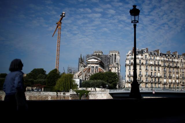 A woman looks at Notre-Dame de Paris Cathedral, which was damaged in a devastating fire one year ago, as restoration work resumes slowly after an interruption due to the lockdown imposed to slow the rate of the coronavirus disease (COVID-19) in Paris, France, April 27, 2020.  REUTERS/Gonzalo Fuentes