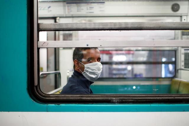 FILE PHOTO: A man wearing a protective face mask rides a metro as a lockdown is imposed to slow the rate of the coronavirus disease (COVID-19) in Paris, France, April 26, 2020. REUTERS/Gonzalo Fuentes/File Photo
