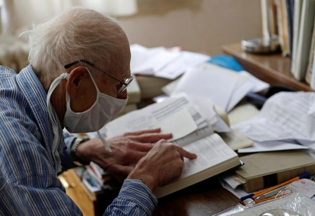 Petr Brandejsky, a 90-year-old Holocaust survivor, reads a book at his apartment as the spread of the coronavirus disease (COVID-19) continues in Prague, Czech Republic, April 24, 2020. Picture taken April 24, 2020.  REUTERS/David W Cerny